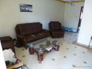 LIving room, looking slightly left from the front door. Kitchen entrance is just visible right of the water bottles.